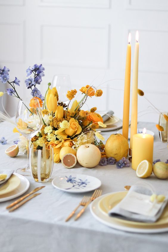 a gorgeous wedding tablescape with a grey tablecloth and napkins, white and gold plates, yellow candles and a yellow floral arrangement