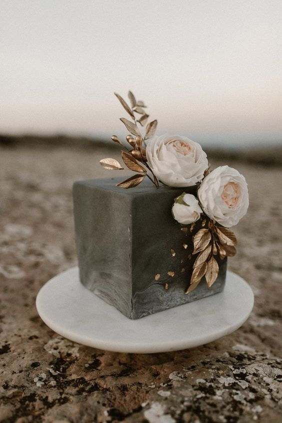 a grey concrete wedding cake decorated with gold leaves, berries and some blush blooms is a masterpiece for a modern wedding