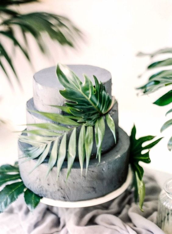 a grey concrete wedding cake decorated with tropical leaves is a fantastic solution for a modern or minimalist wedding