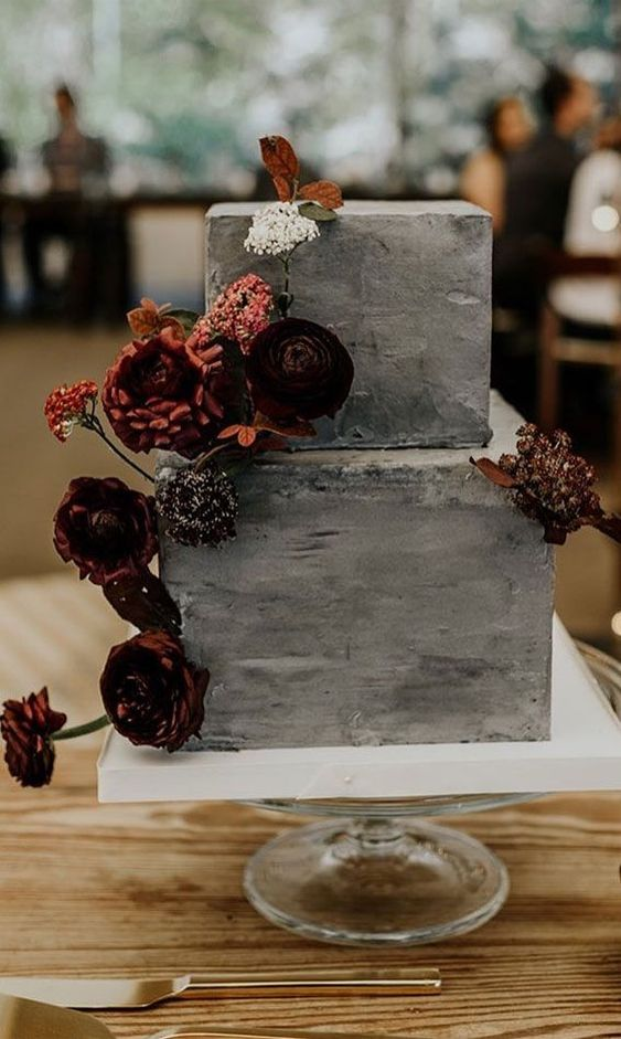 a grey concrete wedding cake with bold dried and fresh blooms and leaves is a stylish wedding dessert idea
