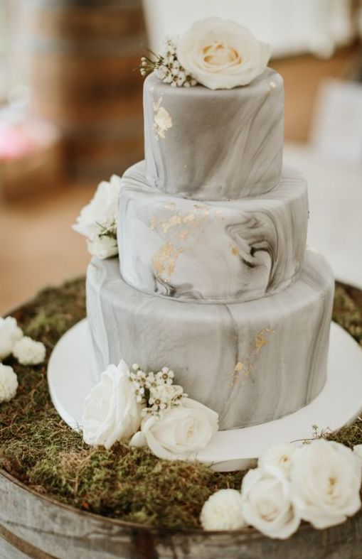 a grey marble wedding cake with gold leaf and white blooms is a stylish and modern wedding dessert idea