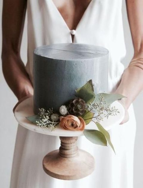a grey one tier wedding cake with dried and fresh blooms and greenery is a modern wedding dessert idea