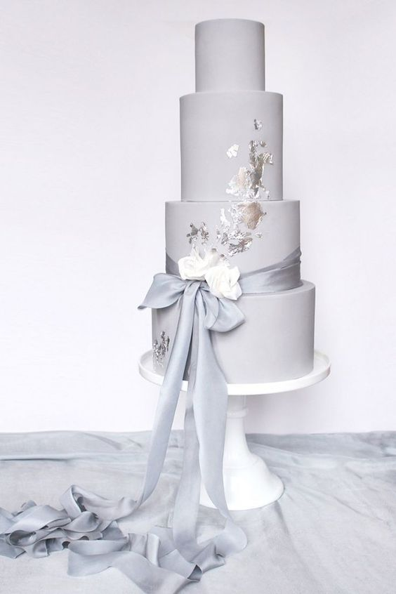 a grey plain wedding cake with silver leaf, white blooms and a long ribbon with a bow is a stylish modern wedding dessert