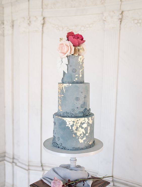 a grey textural wedding cake with gold leaf, bright sugar blooms and gilded leaves is a very refined and formal wedding dessert
