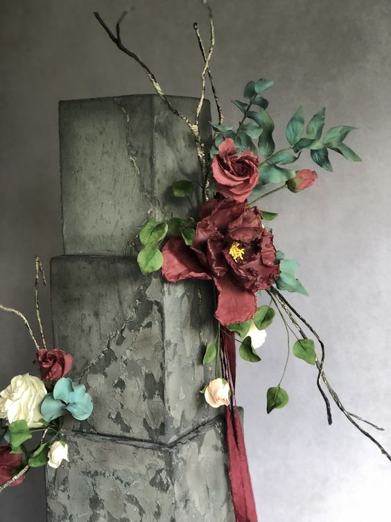 a grey textural wedding cake with gold touches, gilded twigs, deep red and white blooms and greenery