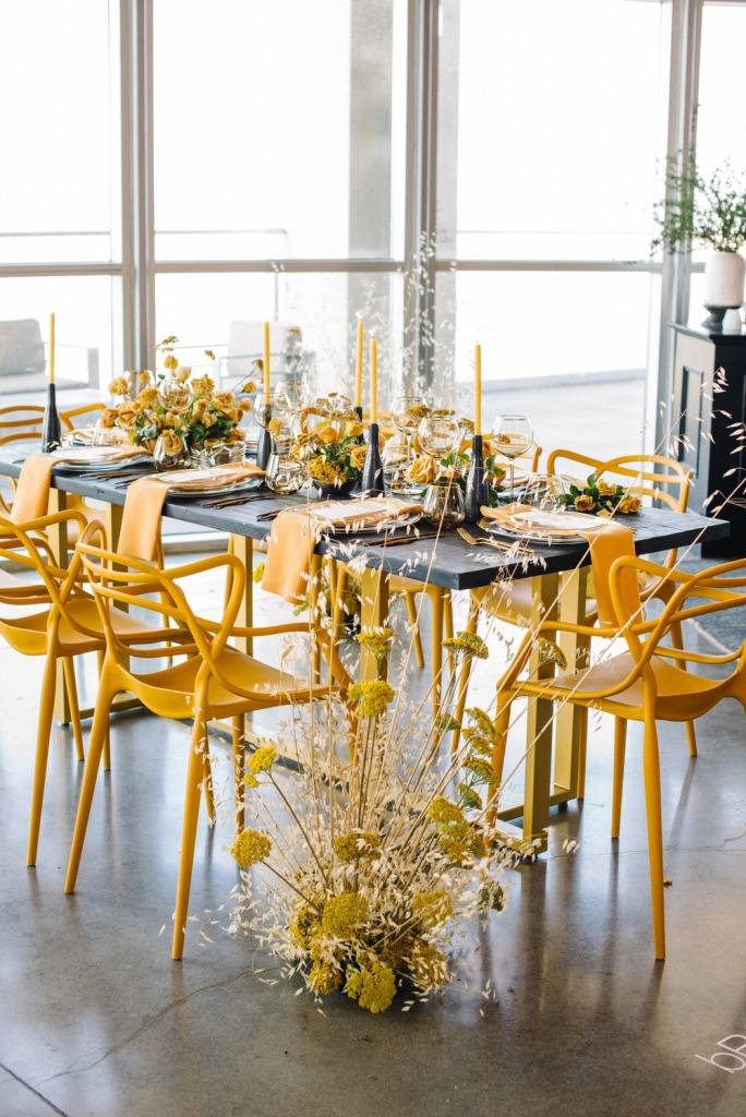 a jaw-dropping wedding tablescape with a grey table and candleholders, yellow candles, blooms and napkins and a floral arrangement by the table
