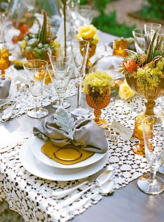 a lovely vintage-inspired wedding table setting with a doily table runner, grey napkis and pale greenery, rust and yellow glasses, blooms and plates