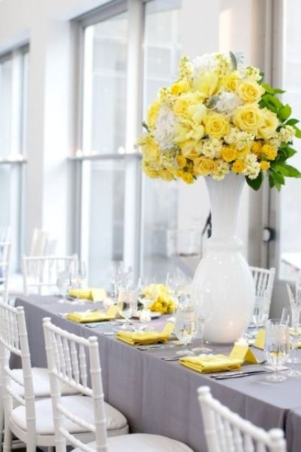 a modern grey and yellow wedding tablescape done with a grey tablecloth, yellow napkins, a bold and tall yellow floral centerpiece