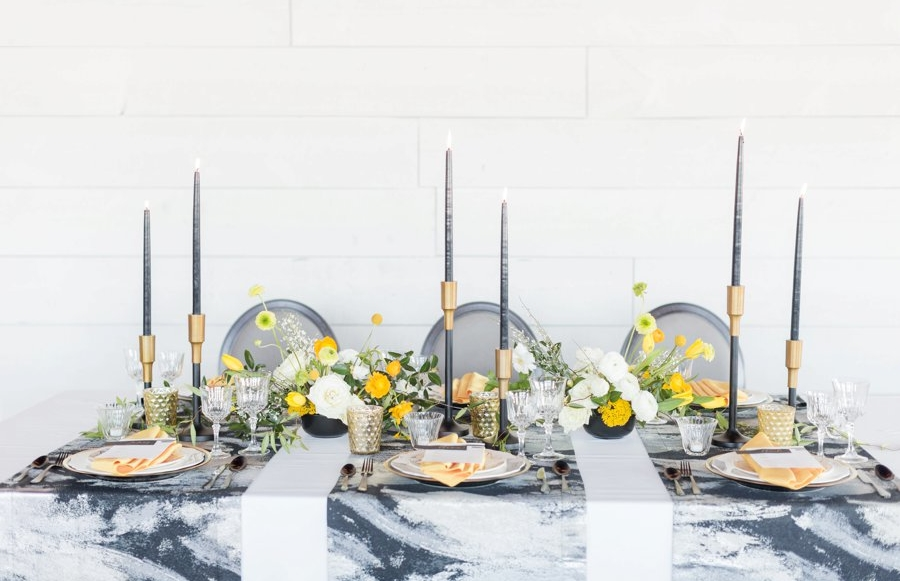 a modern wedding tablescape done with a grye marble tablecloth, grey candles, gold candleholders, chargers and bold yellow blooms