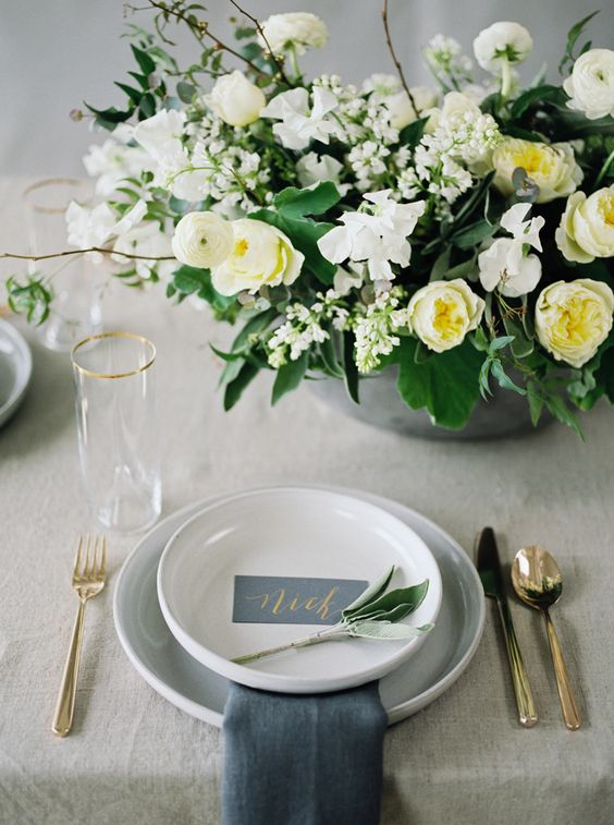 a refined wedding table setting with a grey tablecloth and napkins, grey porcelain, a vase with white and yellow blooms and much greenery