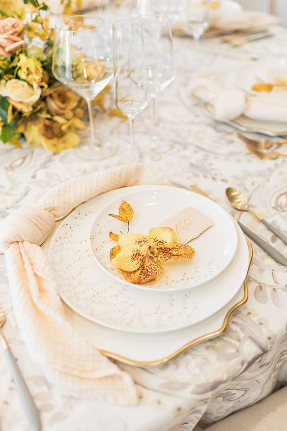 a refined wedding tablescape with a grey printed tablecloth, printed porcelain, peachy napkins and yellow blooms