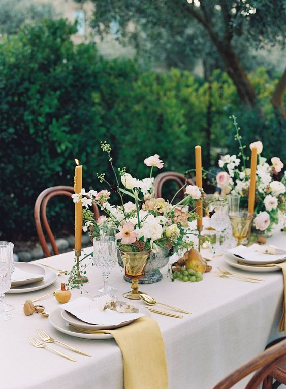 a romantic wedding tablescape with a dove grey tablecloth, mustard napkins, neutral stationery, blush blooms and yellow candles