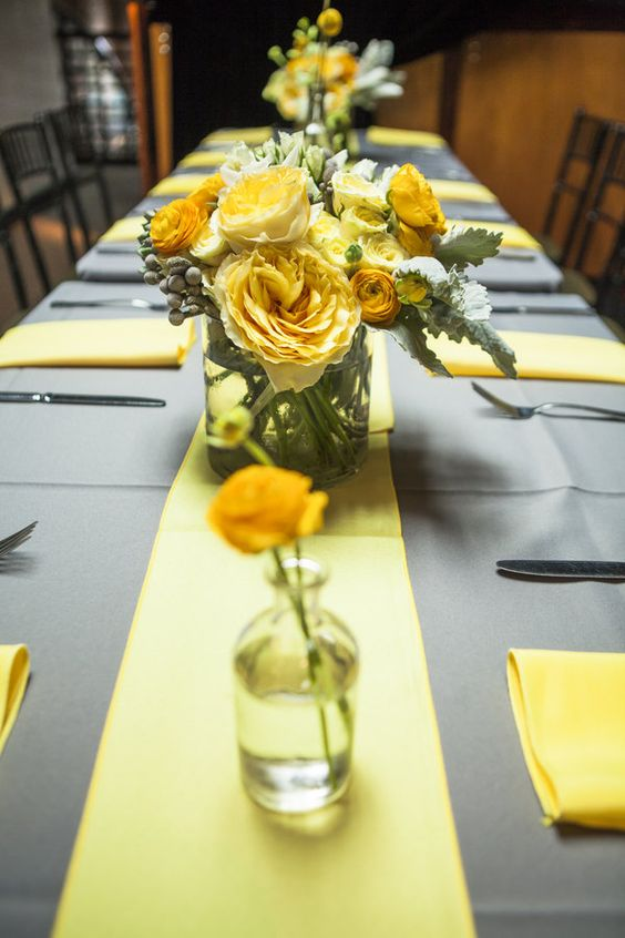 a simple and modern wedding tablescape with a grey tablecloth, yellow napkins and a table runner and bold yellow blooms