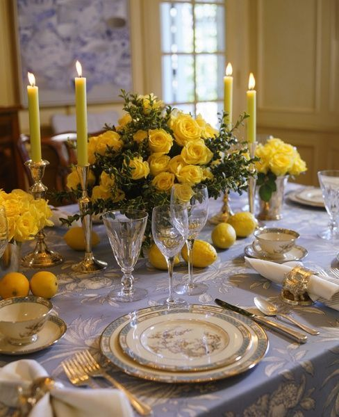 a sophisticated wedding tablescape with a grey printed tablecloth, some elegant porcelain, bold yellow blooms, candles and lamons on the table