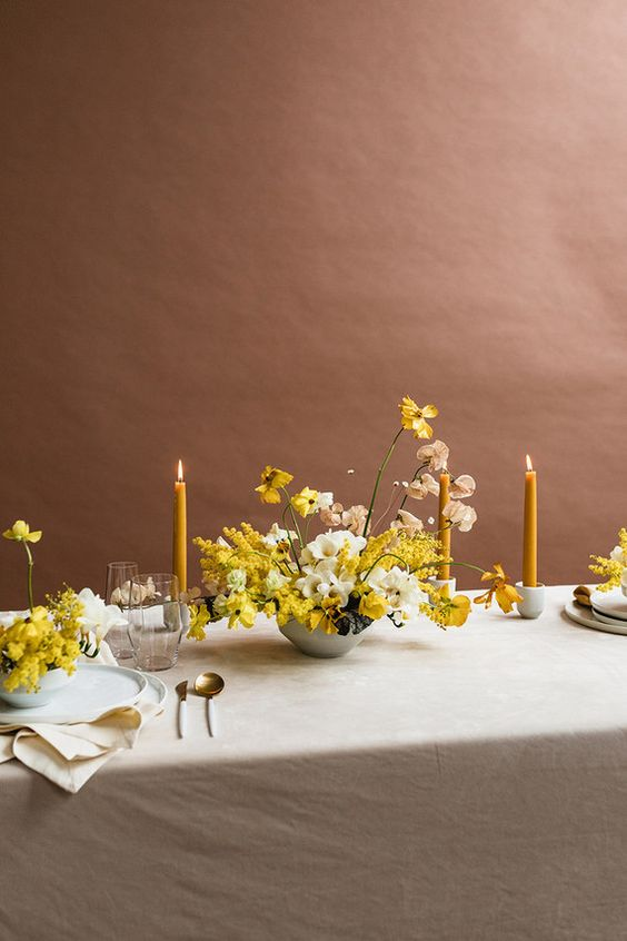 a stylish modern wedding table setting with a grey tablecloth and napkins, white porcelain, yellow candles and blooms