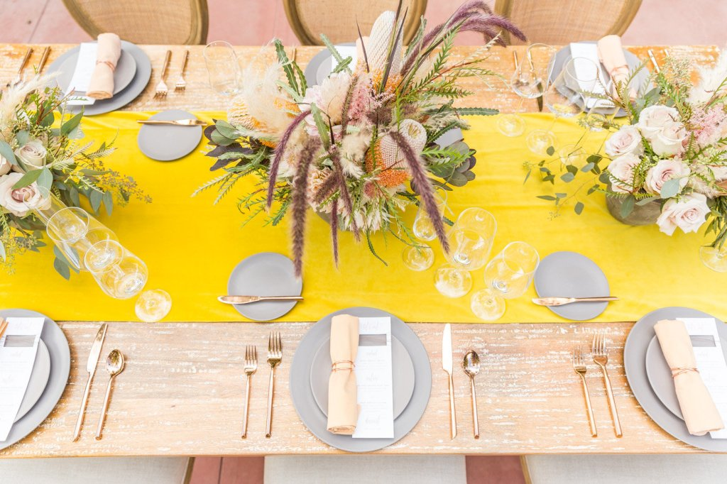 a stylish modern wedding tablescape with a yellow table runner, grey plates and chargers, blush blooms and greenery and gold cutlery