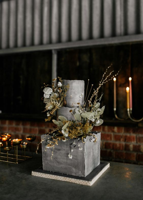 a textural grey square and round wedding cake with dried blooms, greenery and some fresh flowers is a real masterpiece