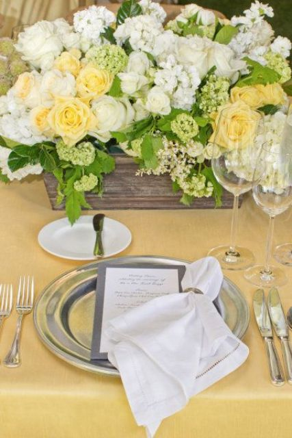 a vintage rustic wedding tablescape with a yellow tablecloth, silver chargers and cutlery, a wooden box with white and yellow blooms