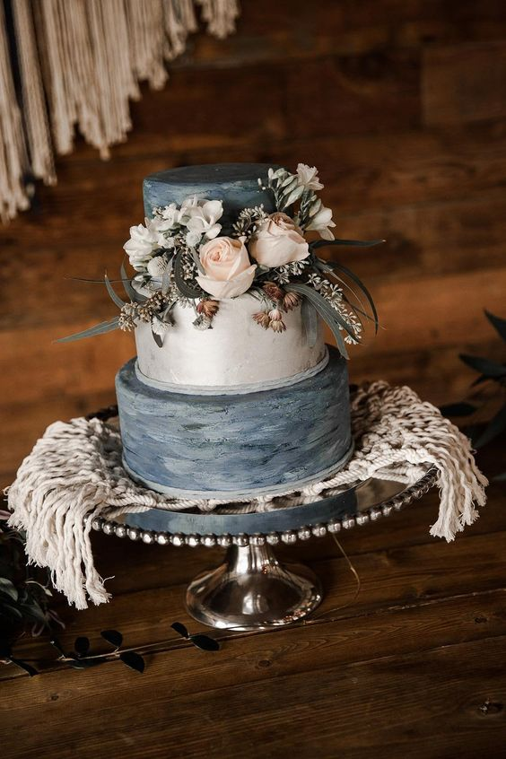 a wedding cake with grey textural and white tier, fresh neutral blooms and greenery and dried flowers