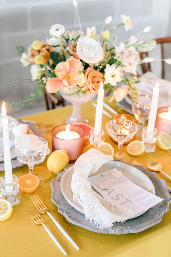 a whimsical wedding table setting with a yellow tablecloth, citrus, candles, grey plates, napkins napkins and a yellow and peachy centerpiece