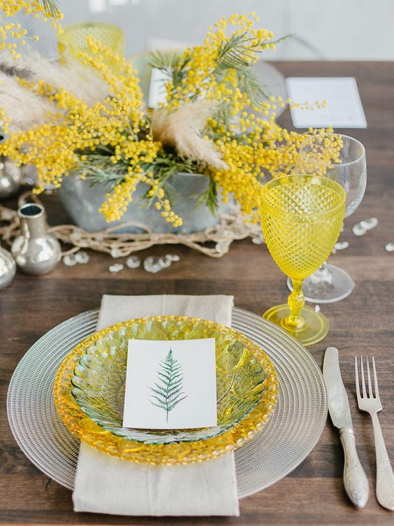 a whimsical wedding tablescape with grey chargers, yellow and green plates, a mimosa and greenery centerpiece and yellow glasses