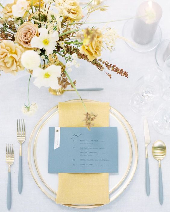 an elegant and airy wedding tablescape with gold edge porcelain and cutlery with grey handles, yellow napkins and a yellow floral arrangement