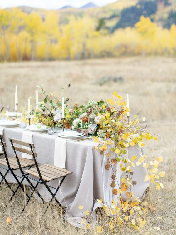 an elegant and chic wedding table setting with a grey tablecloth, white plates and textiles, green and yellow blooms and leaves