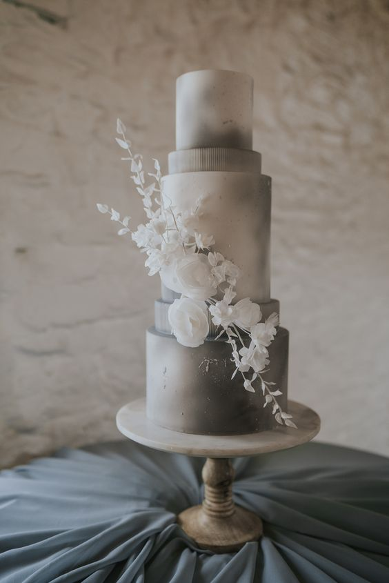 an elegant grey and white watercolor wedding cake with white sugar blooms is a cool and very sophisticated option