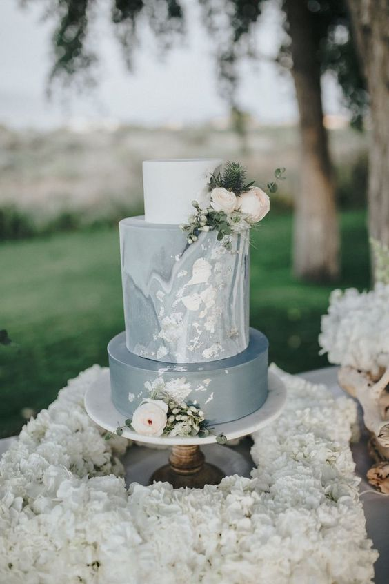 an elegant plain grey and marble wedding cake with neutral blooms and greenery is a very stylish idea