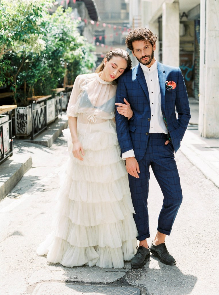 The bride was wearing a ruffle tiered skirt and a sheer high neck top, the groom was wearing a navy plaid suit, grey shoes and a white shirt