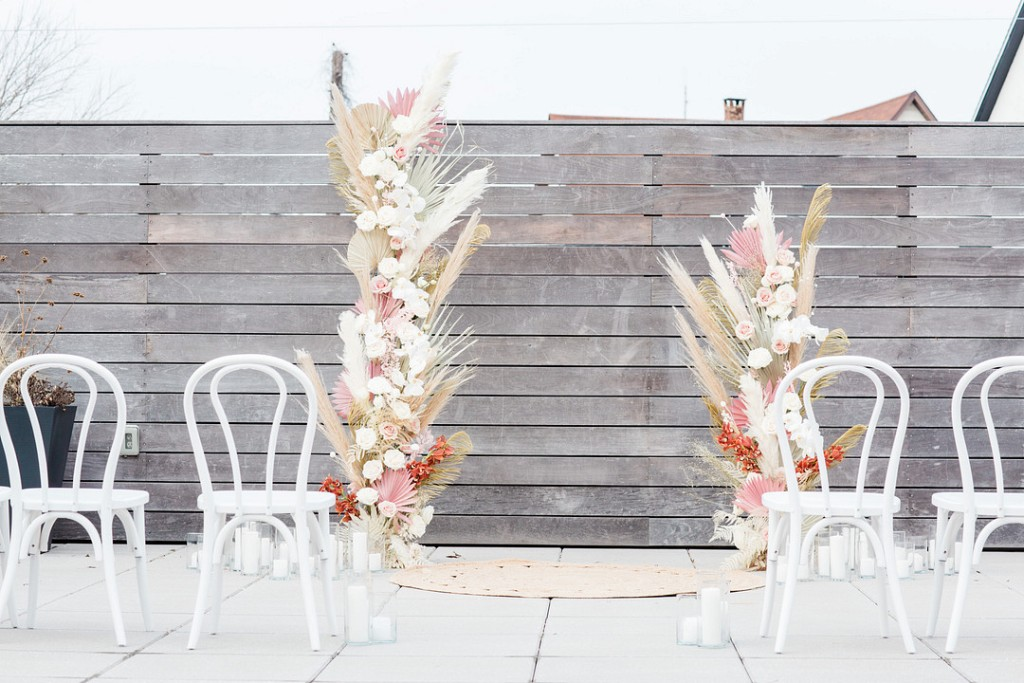 The wedding altar is done with fronds, pampas grass, blush roses and candles all around