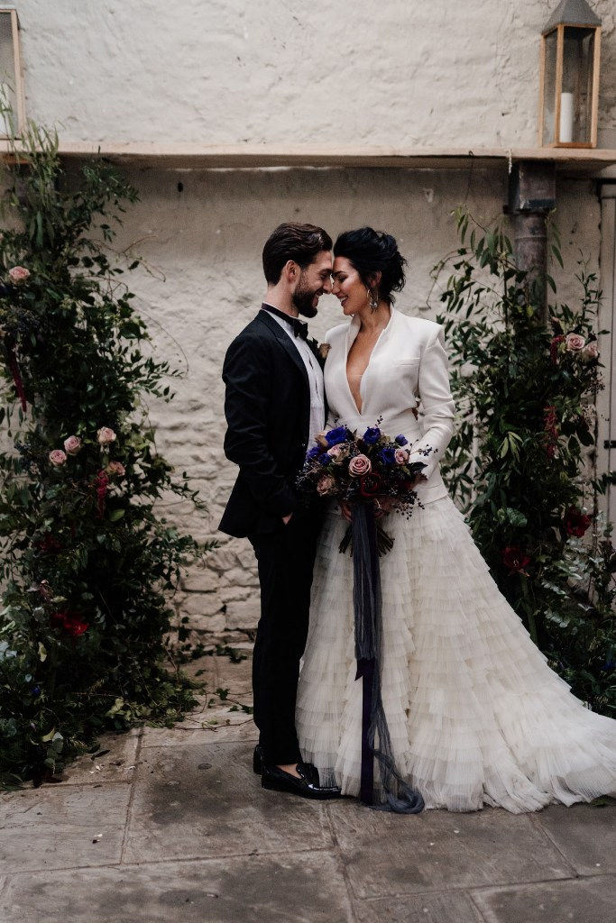 The wedding altar was done with lush greenery and bold blooms, and the bride was wearing a white blazer with a ruffle A-line skirt