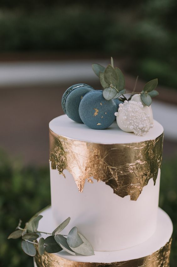 a white wedding cake with gold leaf, blue and white macarons and eucalyptus looks very edgy