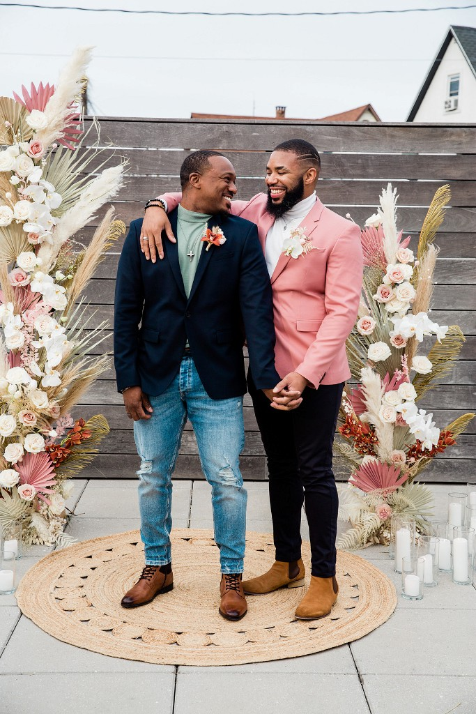 One groom was wearing a green turtleneck, a navy blazer, blue jeans and brown shoes, the second one was wearing a white turtleneck, black jeans and a pink blazer
