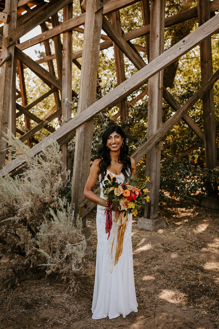 The first wedding dress was a spaghetti strap embellished one, and the wedding bouquet was super bold to contrast