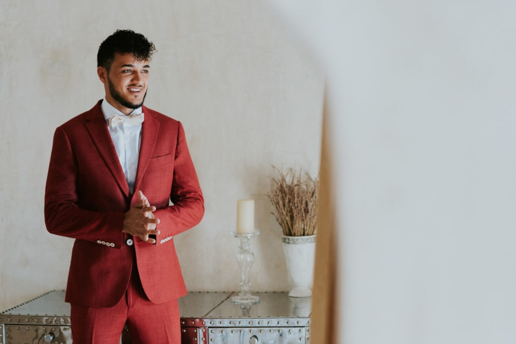 The groom was wearing a red wedding suit, a white bow tie and white plus creamy shoes