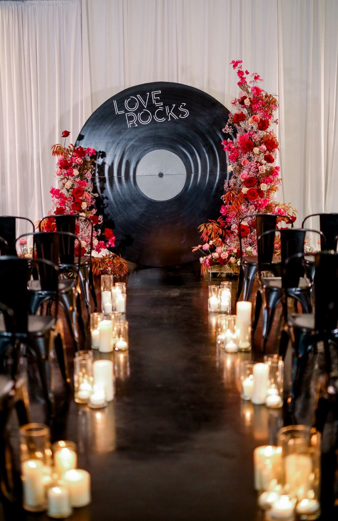 The wedding ceremony space was done with a vinyl backdrop, bold blooms and candles