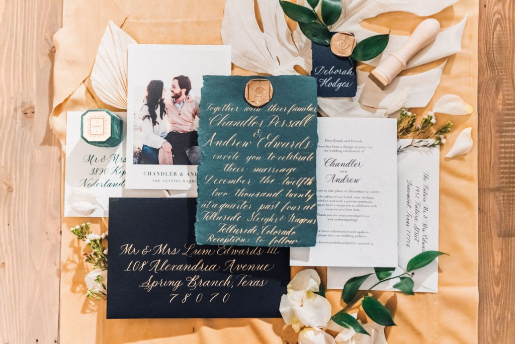 The wedding invitation suite was done with black, green and neutral pieces, with gold calligraphy