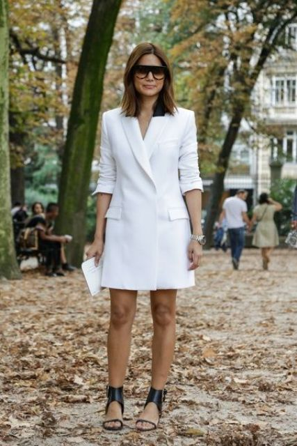 a white over the knee minimalist blazer dress, statement strappy black heels and sunglasses