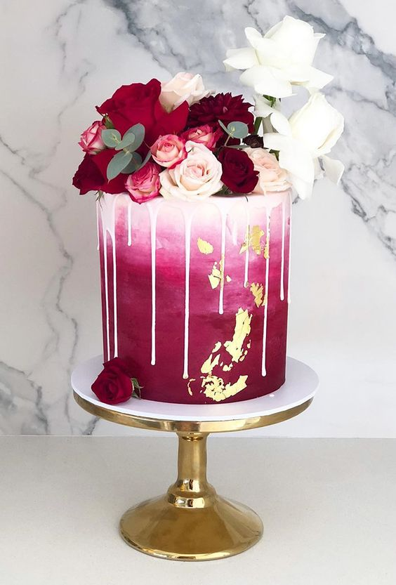 an ombre white to fuchsia wedding cake with drip, gold leaf, red, burgundy and white roses and eucalyptus