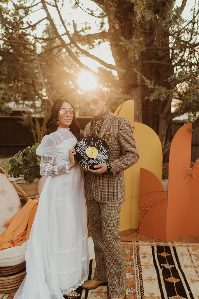 The bride was wearing a vintage wedding dress with floral appliques and puff sleeves, the groom was wearing a plaid suit with a floral shirt and tan shoes