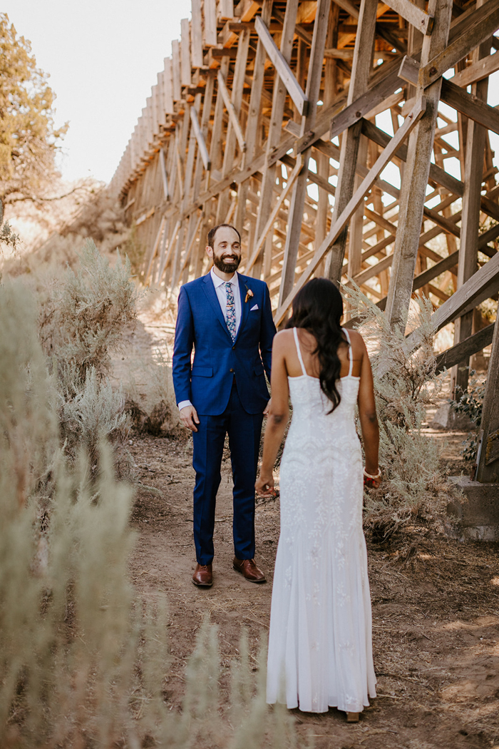 The groom was wearing a blue suit, a white shirt and a floral tie, brown shoes and a bold boutonniere
