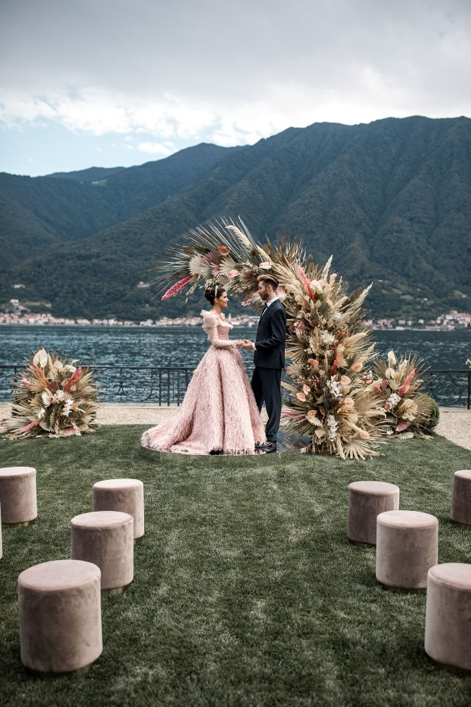 The wedding arch was done with pink touches and dried palm leaves in various colors, with a gorgeous view