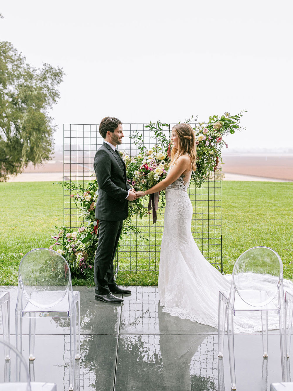 The wedding backdrop was an ethereal floral and greenery one made on a grid, and the chairs were ghost ones