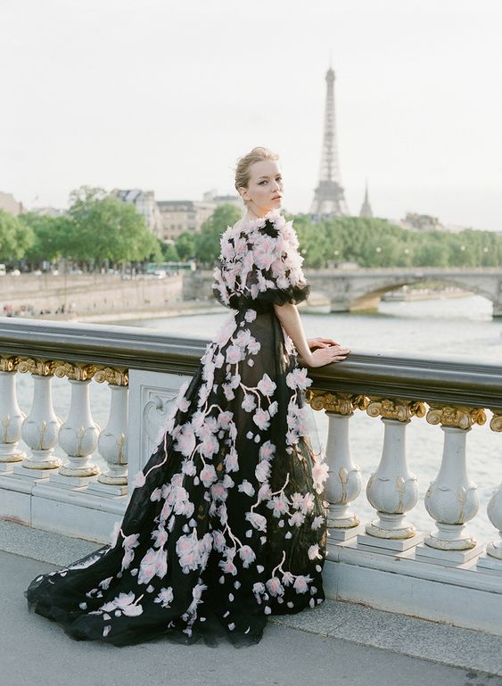 a black wedding ballgown with pink floral appliques and a matching coverup on the shoulders is a refined and haute couture idea