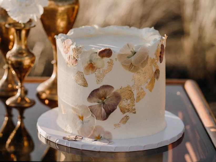 a white wedding cake with a rough edge, pressed blooms and gold leaf is a very refined and chic idea
