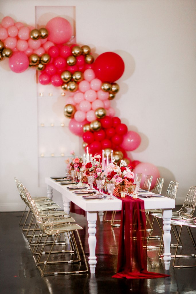 The reception space was accented with bold balloons and bold blooms plus candles