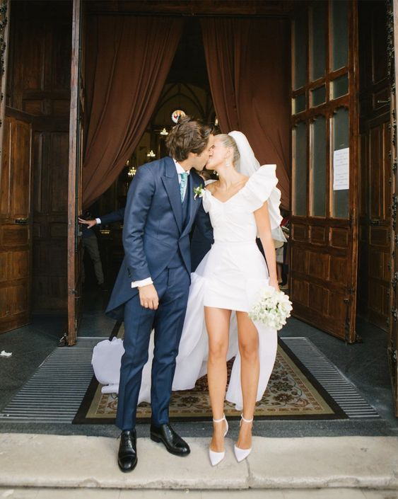 a chic high low wedding dress with a ruffle neckline and a long train, white heels and a veil for a playful and sexy look