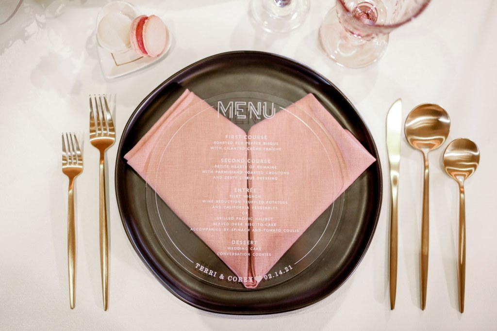 The place settings were done with pink napkins, black chargers and goldd cutlery