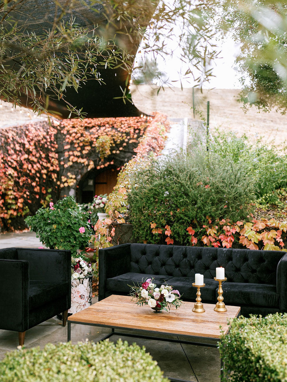 The wedding lounge was a refined one, with black furniture, lush florals and greenery and candles